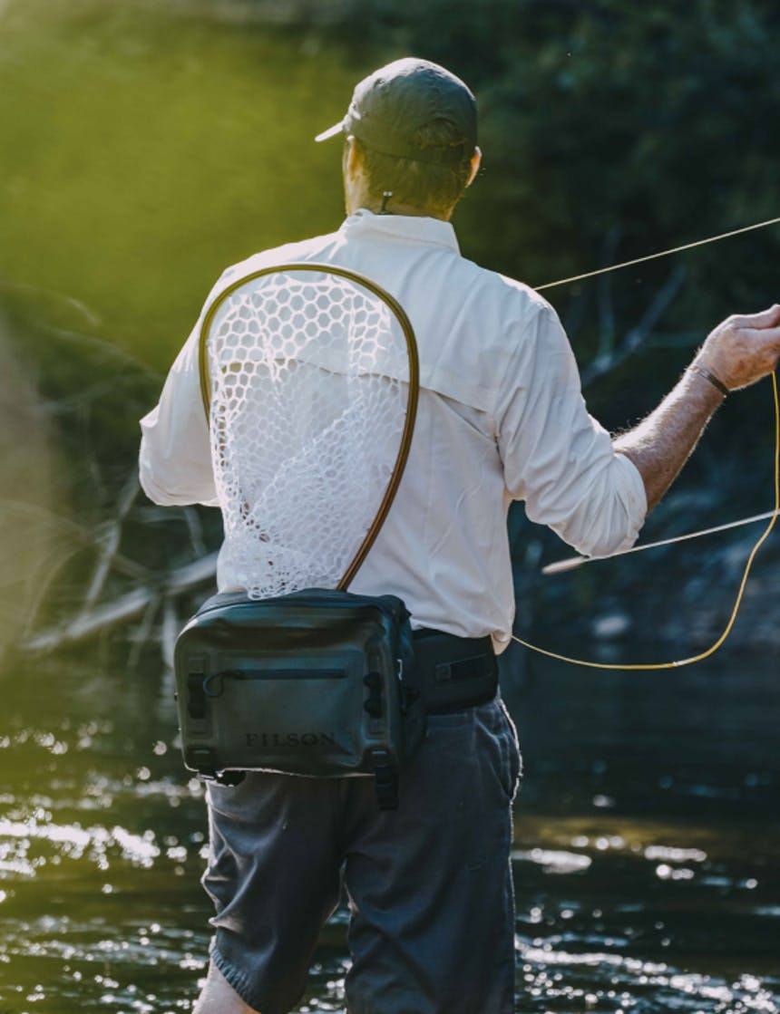 view from behind a white man wearing a white long sleeve button up with the sleeves rolled, dark grey shorts, a green dry waist pack with a wooden fishing net tucked in while he casts a fly fishing rod standing in a river