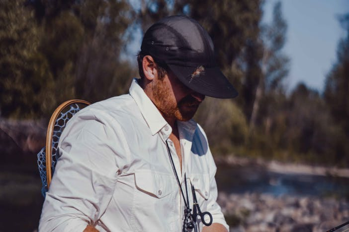 a side view of a white fisherman wearing a white button-up, black duck billed brim with a fly stuck in it and the landing net tucked into his waist pack