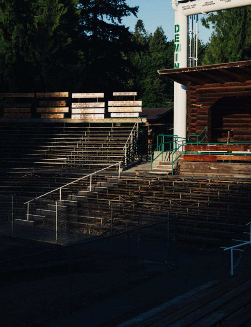 sun hitting empty bleachers in an outdoor arena with wooden bleachers and white and green railings