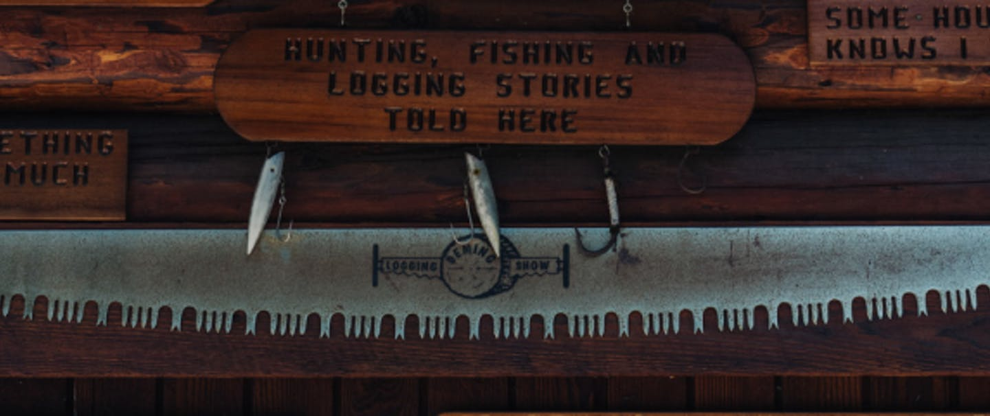 two antlers mounted to wooden blocks above an old metal handsaw with The Deming Log Show printed on it along with several wooden planks with different logging sayings on them