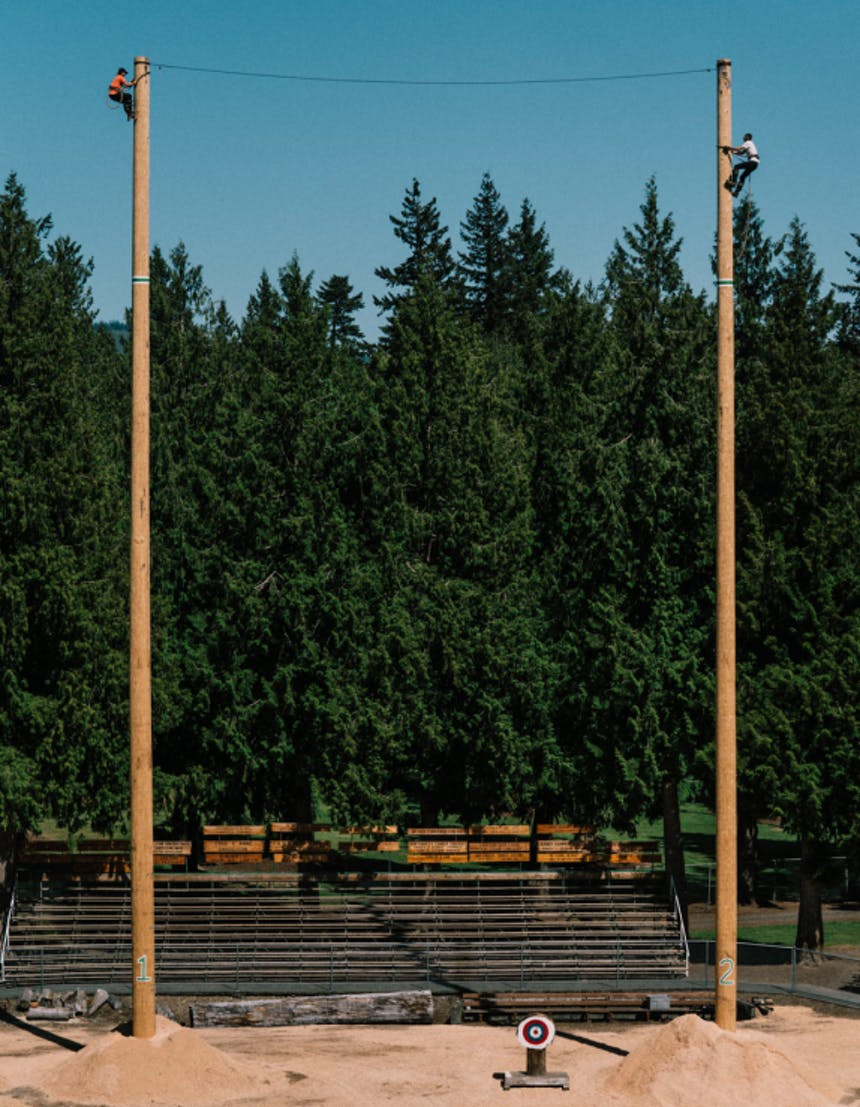 a far view of two men scaling 2 90 foot tall poles inside the outdoor sports arena