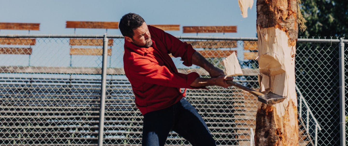 Male wearing red Filson button up shirt swinging an axe into a wood post with bleachers in the distance behind him