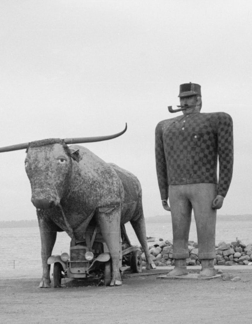 black and white historical image of a statue of Paul Bunyan standing next to babe the ox, who is standing over an old model t car, both next to a sign that reads Paul Bunyan 1937 along a lakeshore