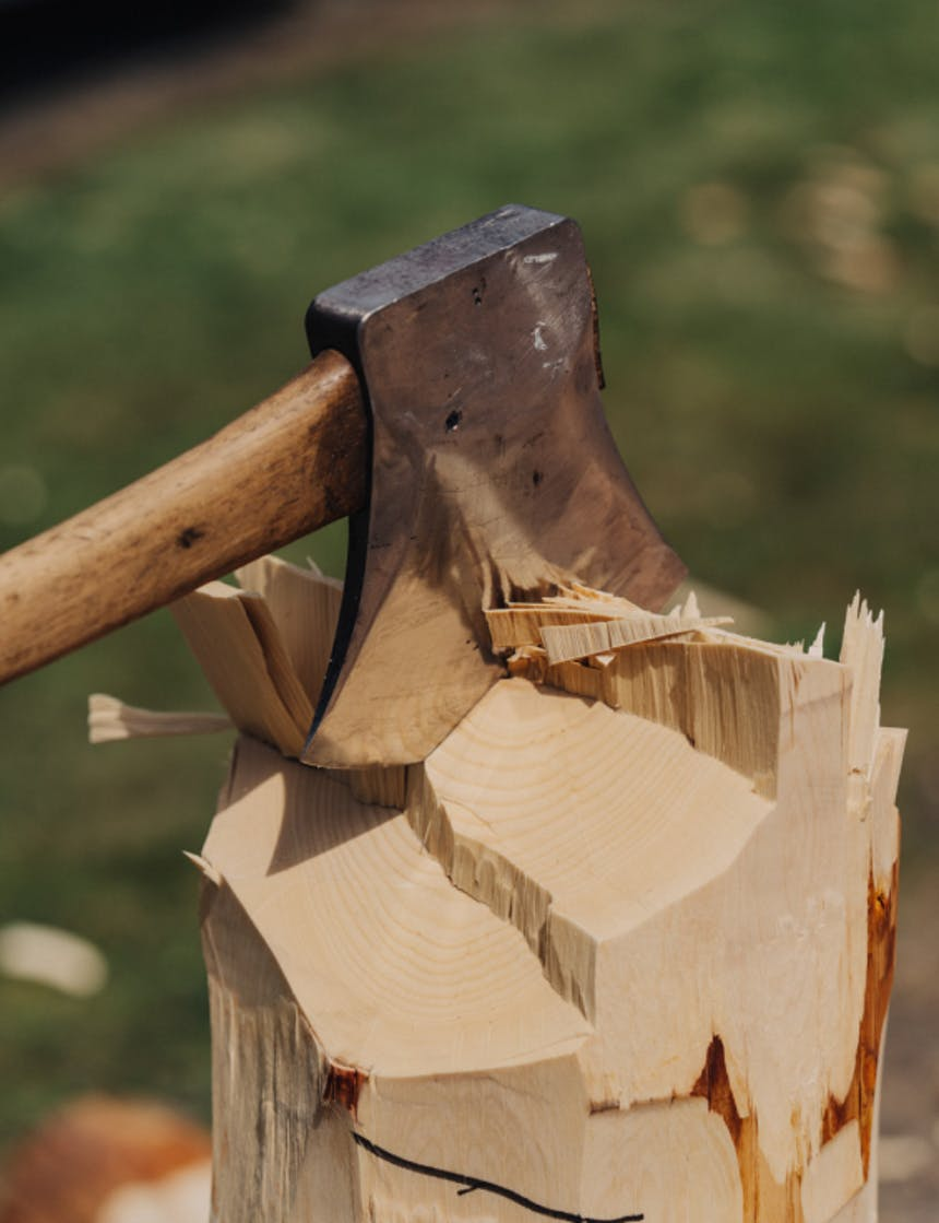 an already chopped wooden post, with clean fresh cuts and jagged edges with an axe stuck in the middle