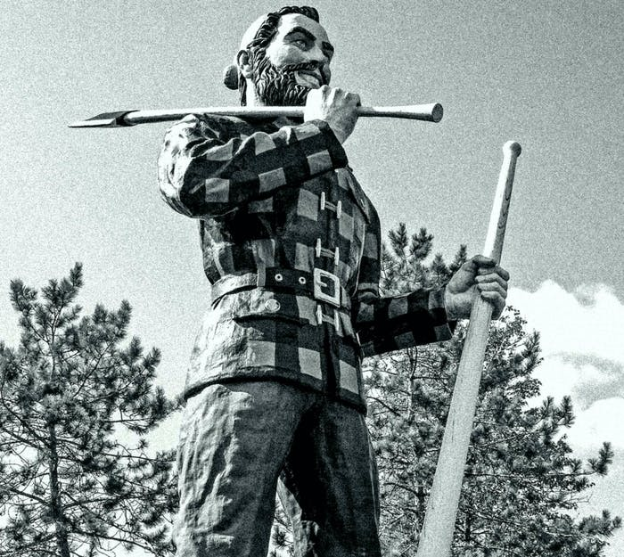 a tall Paul Bunyan statue wearing a flannel and hat, holding an axe over his shoulder and another in the opposing hand towards the ground