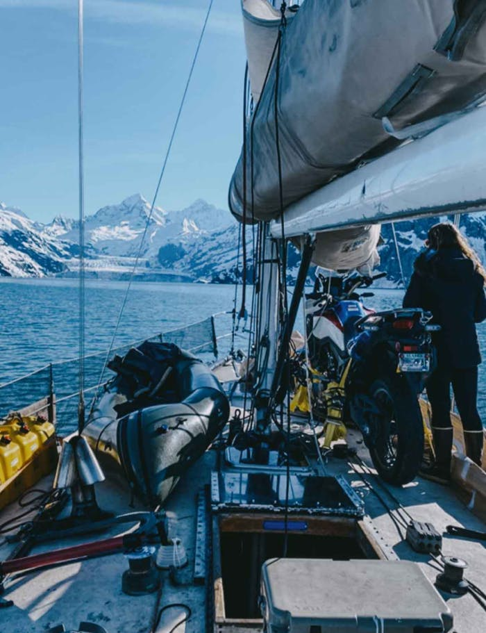 view from the deck of a working sailboat that has gear and a motorcycle strapped to the deck while a woman looks out to the snowy mountains