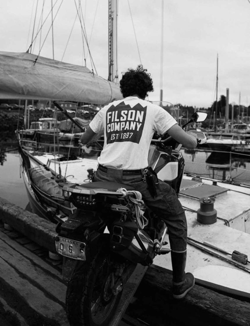 a black and white image of man driving his motorcycle onto the deck of a sailboat from a wooden dock