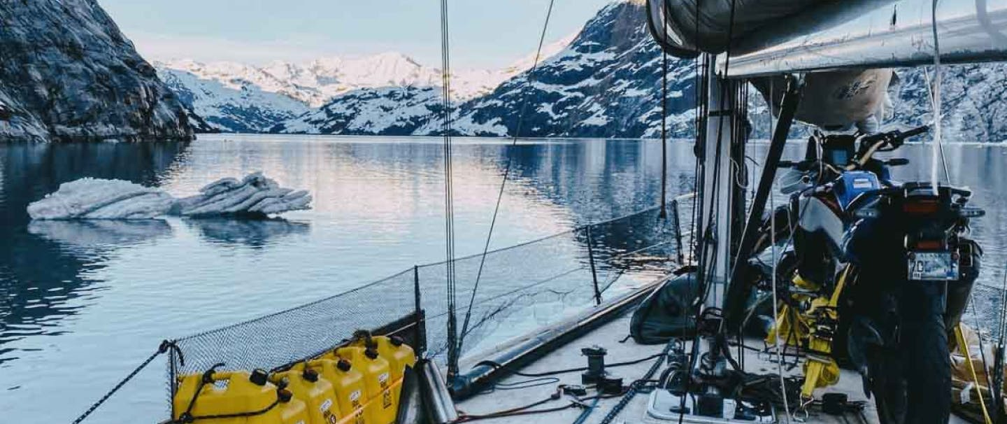 view from the deck of a working sailboat that has gear and a motorcycle strapped to the deck looking out to the snowy mountains