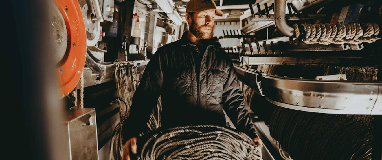 Male on a fishing vessel wearing a black Filson jacket.