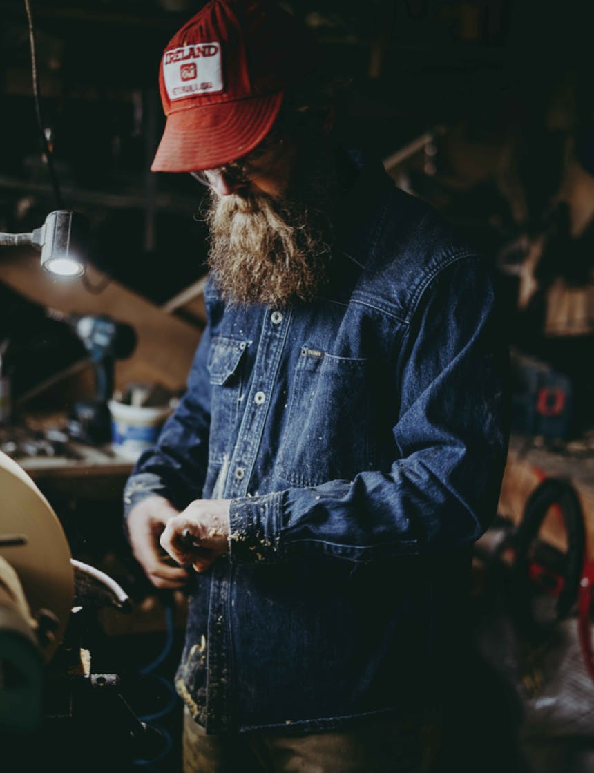 a middle aged bearded white man wearing a denim shirt, dark jeans and red baseball cap standing in his woodshed holding a tool to start carving a piece of wood into a bowl