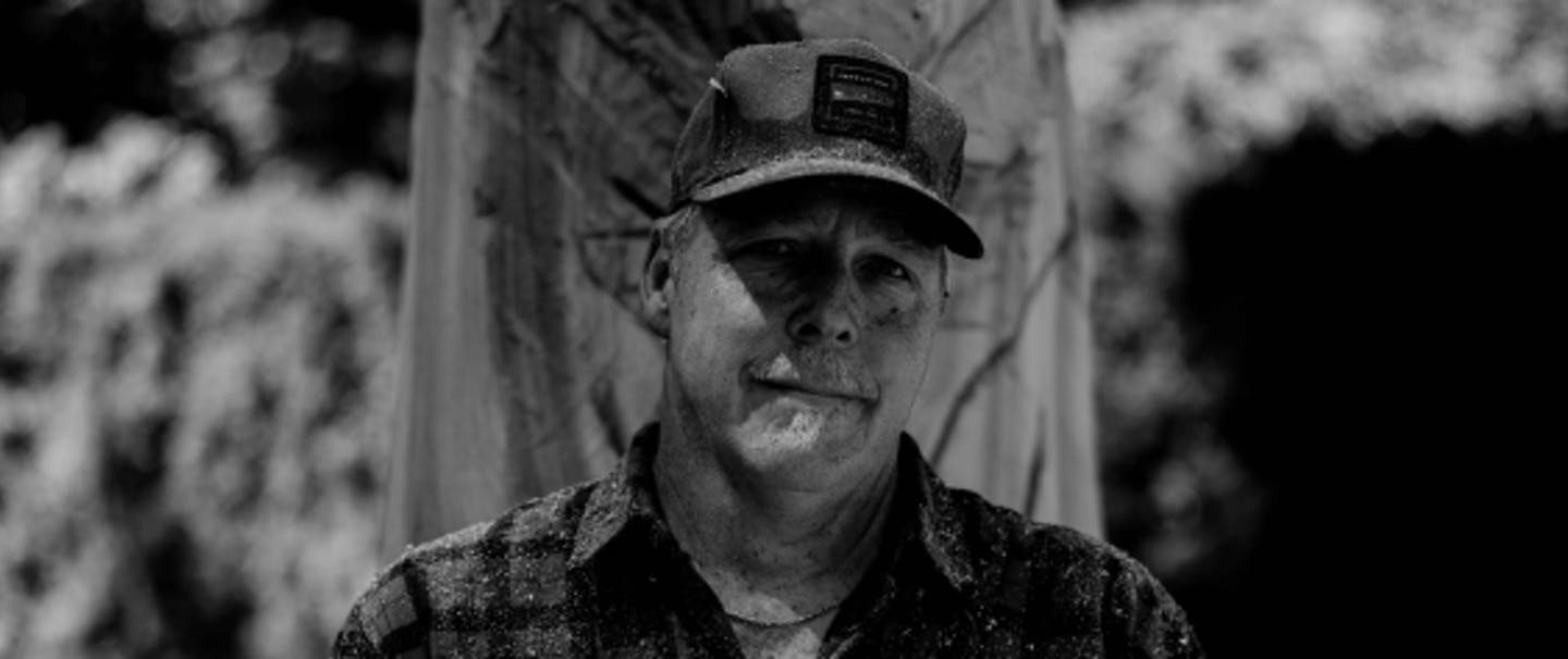 black and white of an older white man wearing a flannel shirt, holding his eye and ear protection standing in front of his wood carving of a bear in progress