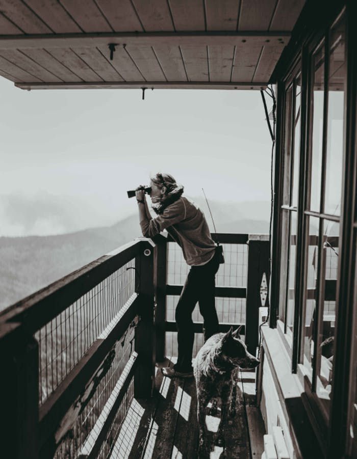 black and white of a woman on the deck of a lookout towner looking out at something through binoculars