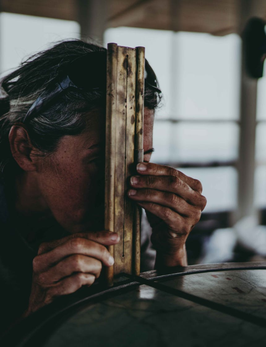 a close up of a grey haired woman looking through a measuring system for wildfires
