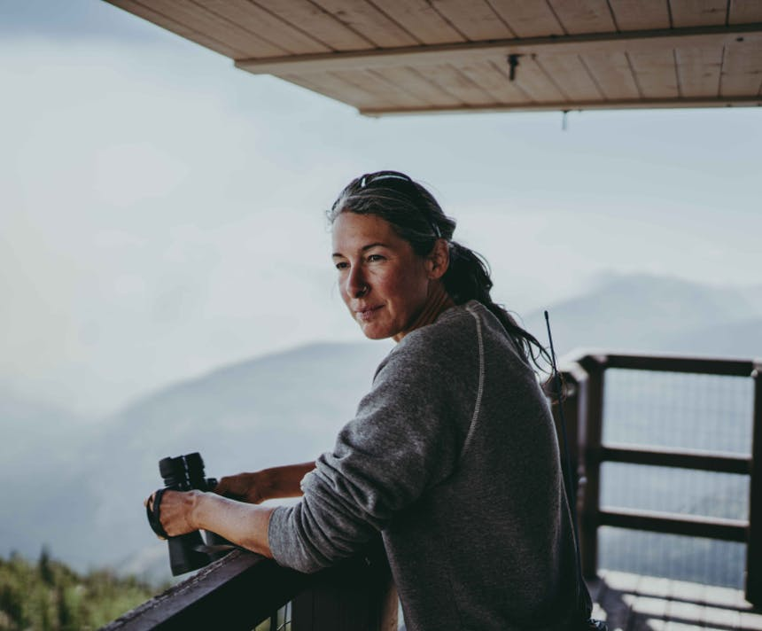 a close up image of a woman wearing grey sweatshirt, holding binoculars standing on the catwalk of a fire lookout tower