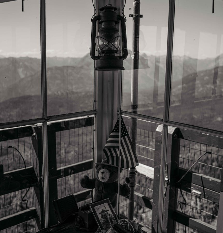 a black and white image where two of the four walls meet in the fire lookout tower, looking out to the mountains