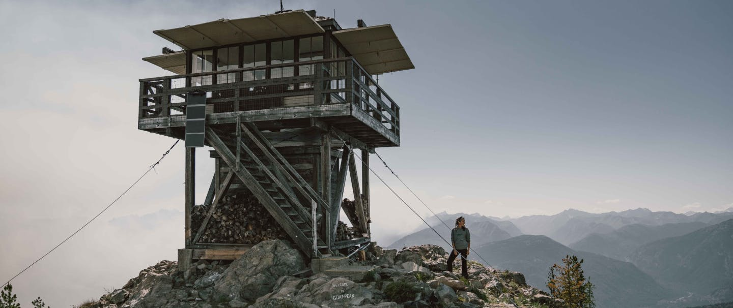 a woman wearing a grey sweatshirt and black pants standing next to her black and grey cattle dog on the of a rocky peak where a fire lookout stands