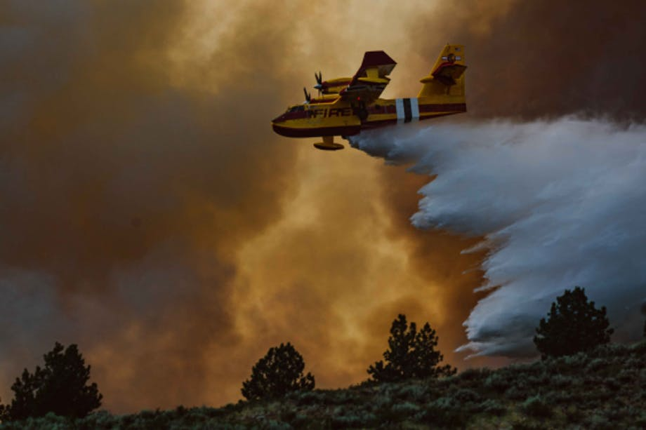an areal photo of a yellow and red forest service plane dropping water on a raging fire above the treelike