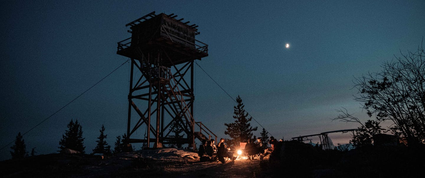 at dusk, a group sits around a lantern at the foot of a 28 foot tall fire lookout tower