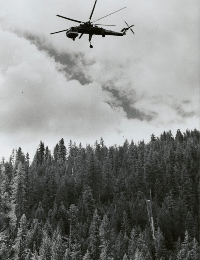a black and white image of a helicopter flying up to pull the hanging log to the drop zone away from the logging site