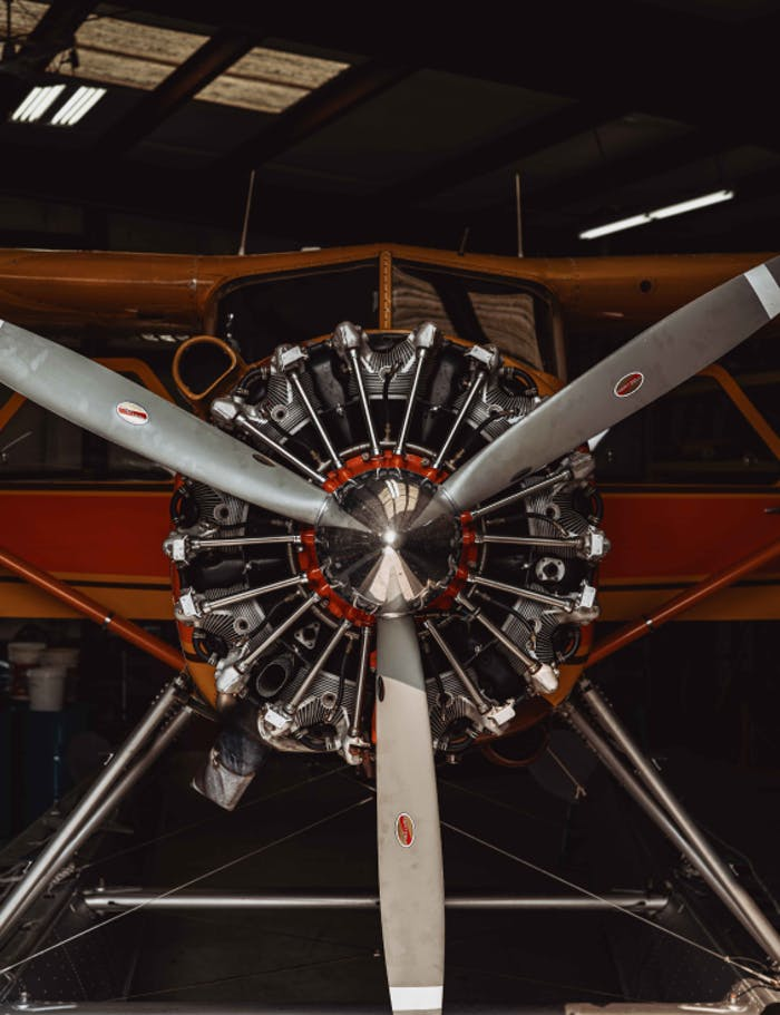 close up image of the front of a orange and red float plane