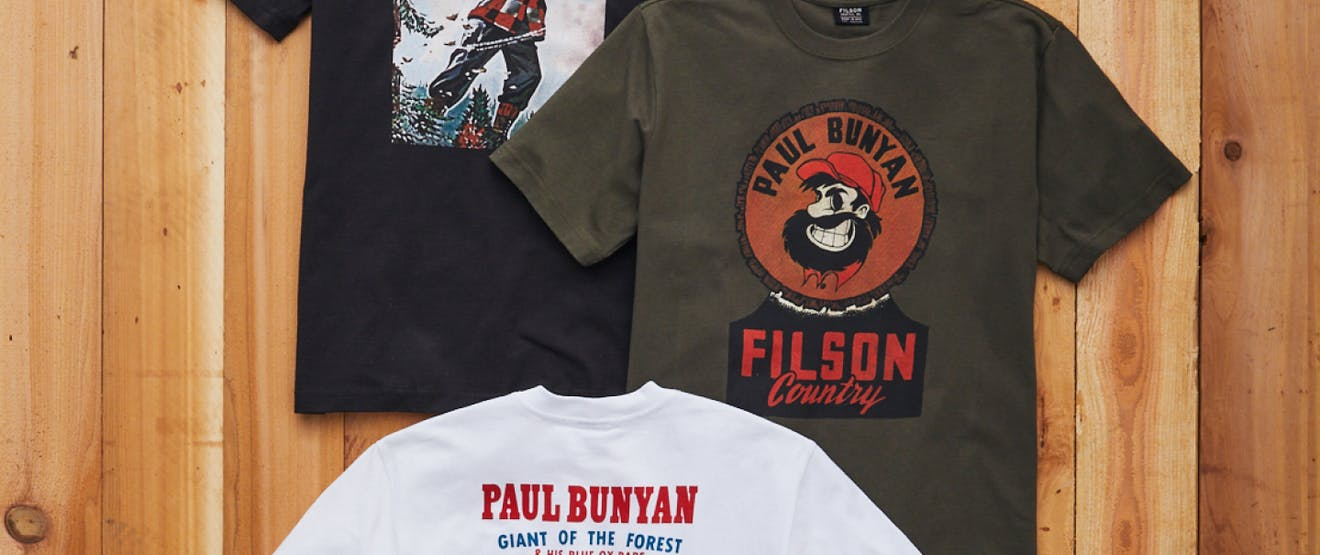 three t-shirts layed down on a wooden surface, one black, one olive green and one white with Paul Bunyan graphics on them