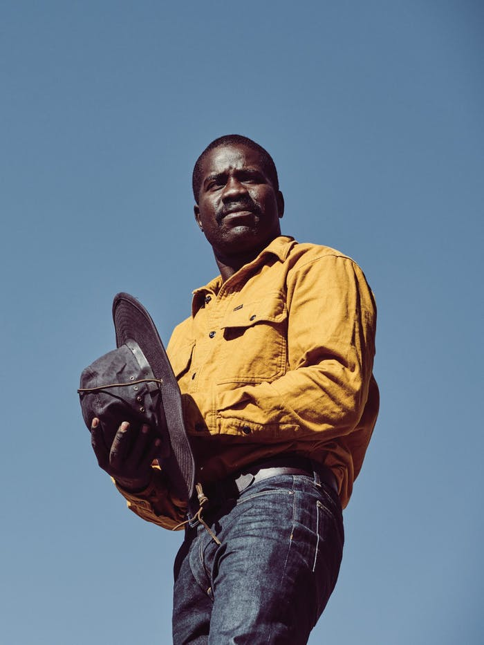 African American man wearing a yellow flannel shirt and holding a oil cloth hat looking off into the distance with a blue sky behind him