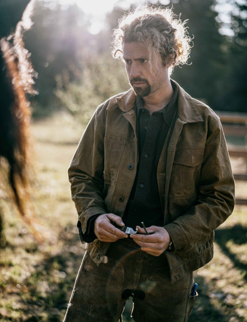a wavy blonde haired man wearing workwear clothes looking at his horse