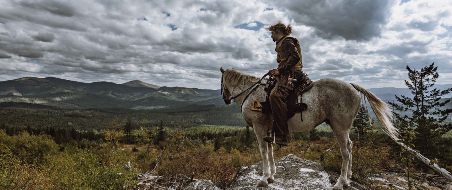 a man sitting in the saddle of a white horse looking off into the distance at the top of a peak towards the far off mountains