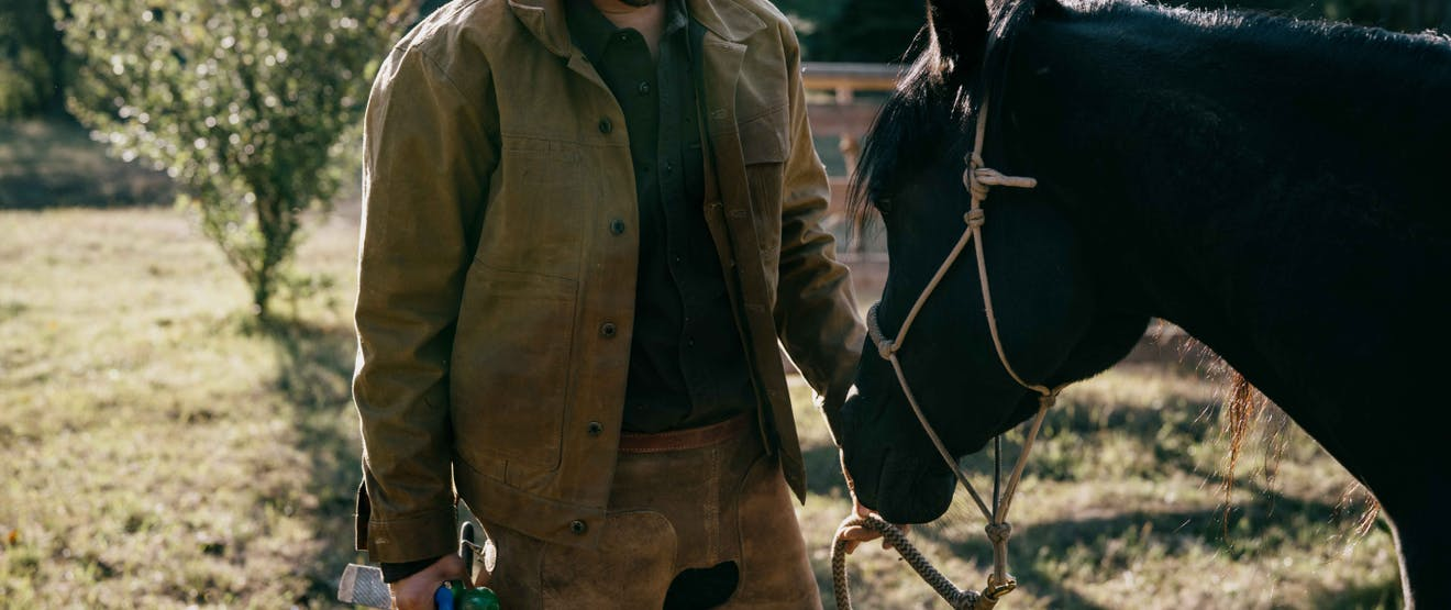a close up of a man wearing workwear holding the lead rope for a black horse in front of him