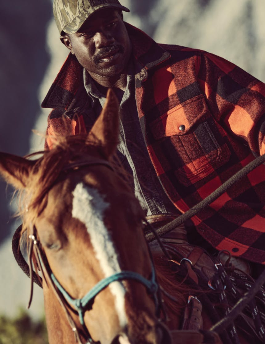 An African American man riding a brown horse wearing a red and black plaid wool coat and camouflage baseball cap