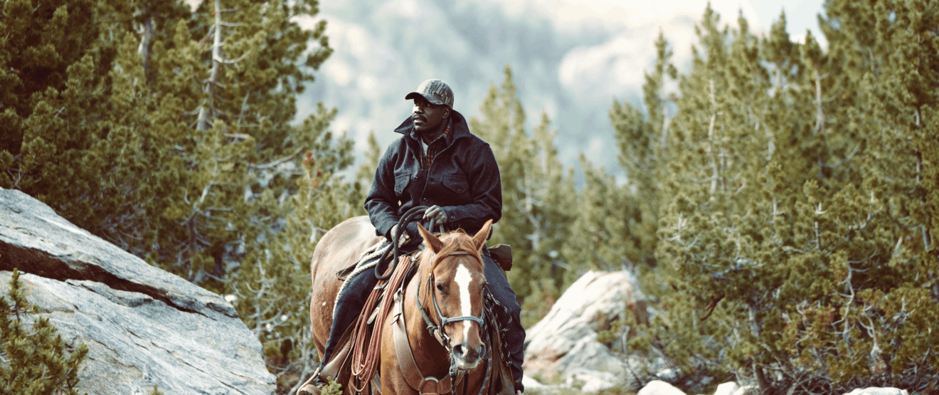 An African American man riding a brown horse wearing a camouflage baseball cap and dark grey wool coat riding through the mountains