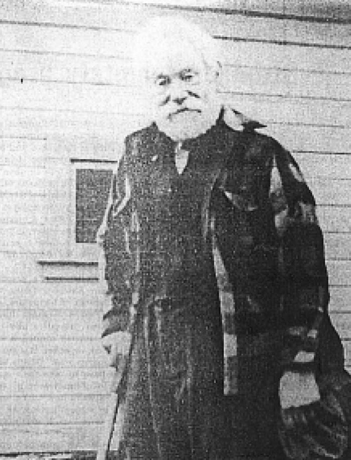 an old black and white pixelated image of a white haired old bearded man, wearing a flannel wool shirt and wool pants standing next to a wood cabin using a cane to hold him up