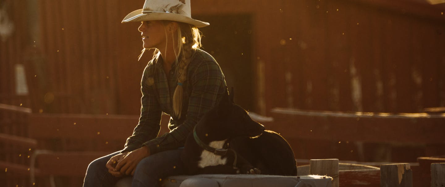 Cowgirl sitting with dog