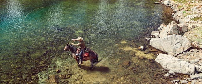 Man fly fishing from a horse in alpine lake