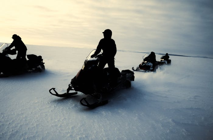 four people on snow machines in the early light of day driving across an ice sheet in Alaska