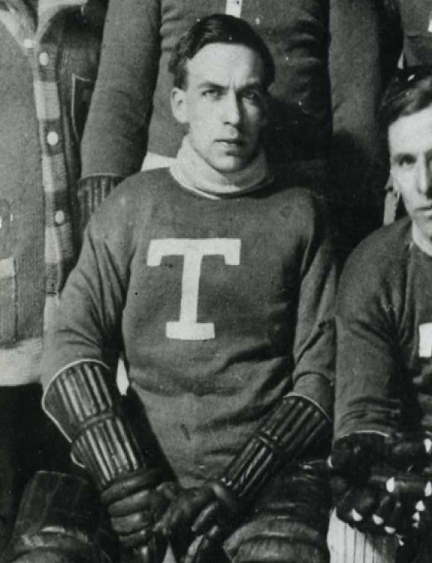 black and white historic photo of a hockey player sitting for a team photo with the letter T on his sweater