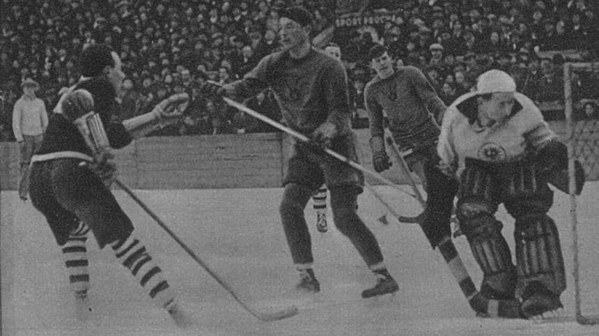 black and white historic photo of men playing hockey in a open air arena