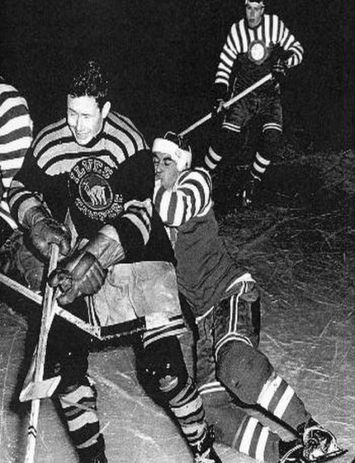 black and white historic photo of hockey players colliding mid ice, one falling behind the other