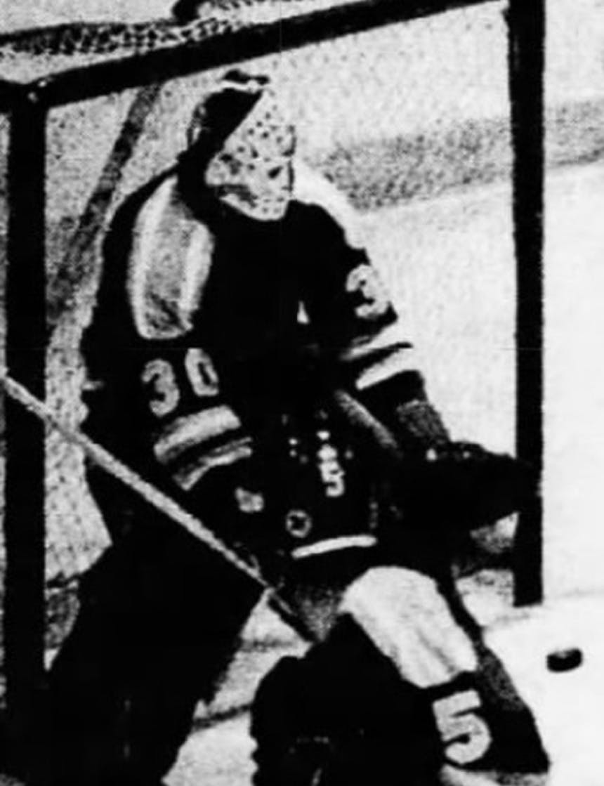 black and white historic photo of a hockey goalie moving in front of an oncoming puck wearing full protection after masks and pads were developed