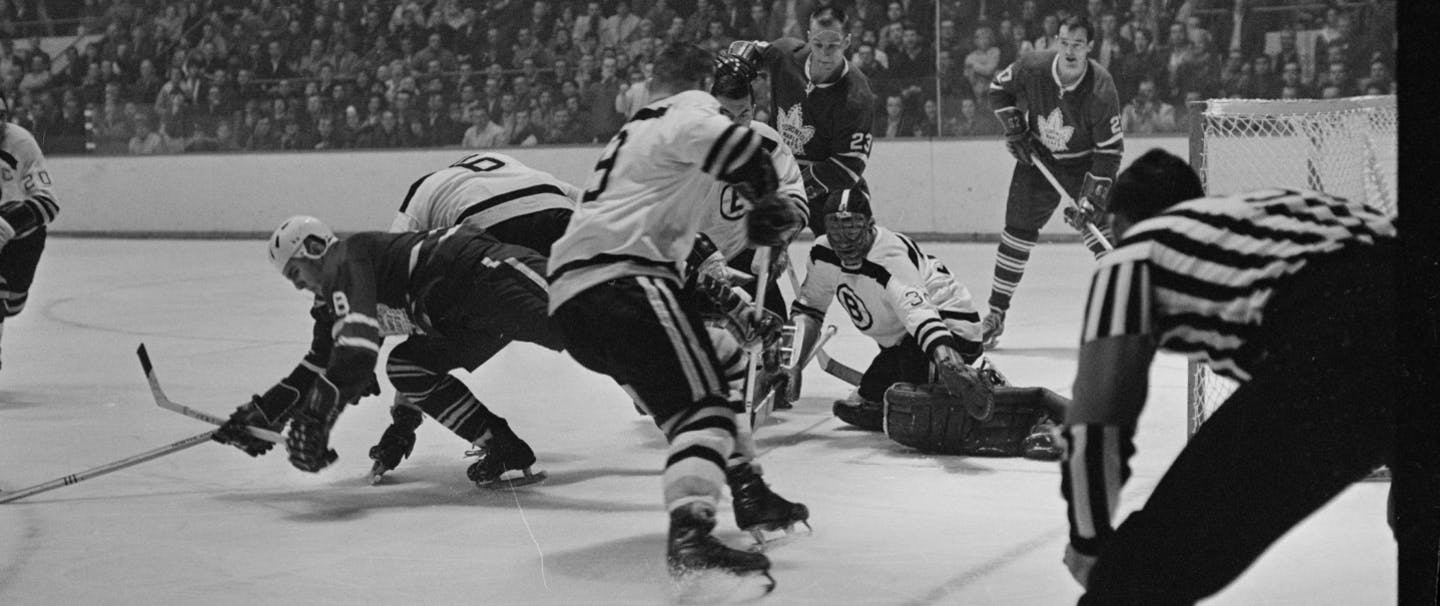 black and white photo of the Boston Bruins and Toronto Maple Leafs hockey teams playing in a arena not wearing helmets