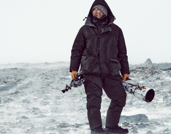 an indigenous man wearing full layers holding camera gear in either hand standing on rocky arctic tundra