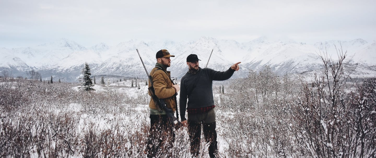 hunters in a snowy field point into distance