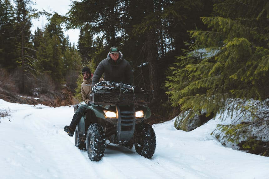 two men riding a four-wheeler through the snow