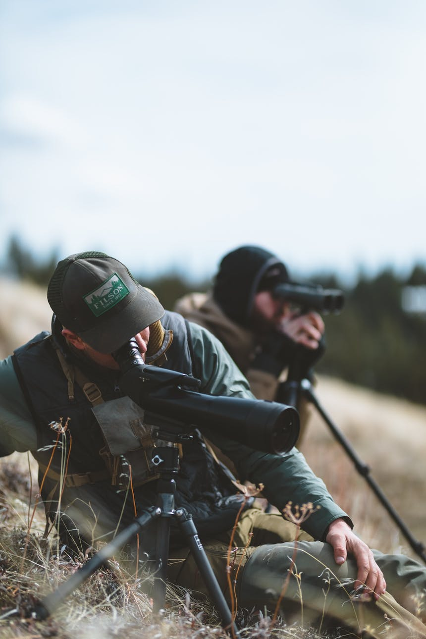two men looking through binoculars