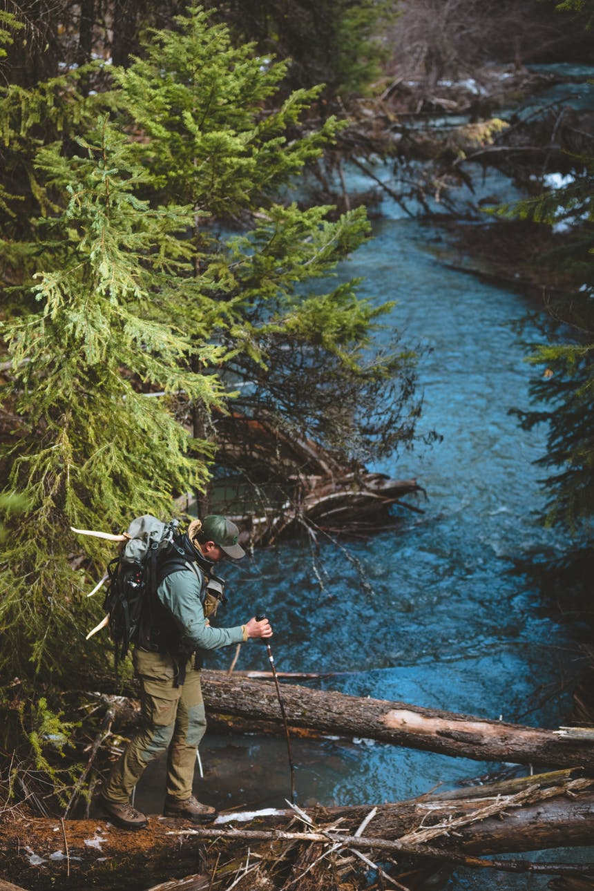 man walking across a log over a creek