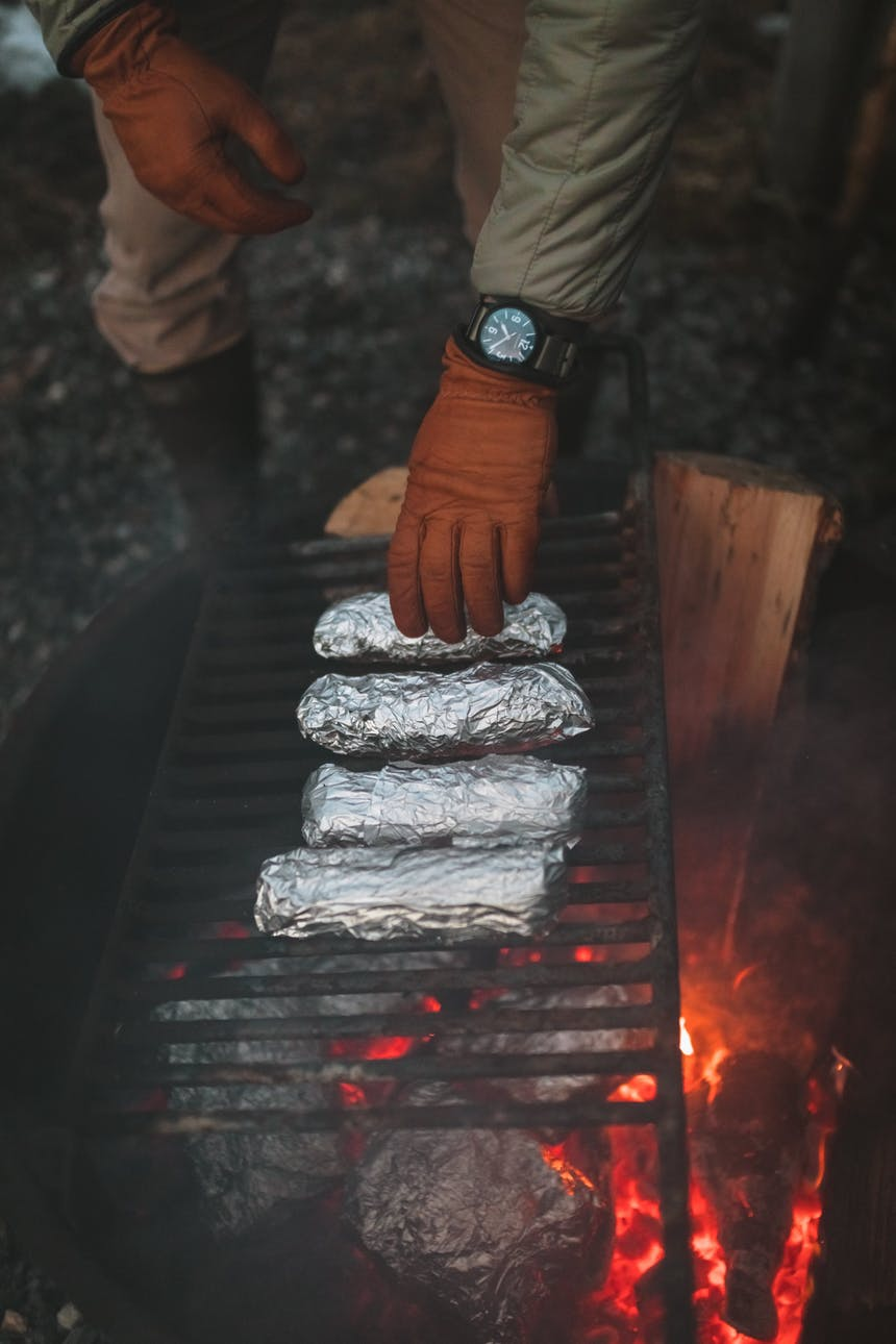 tinfoil dinners placed on campfire to cook