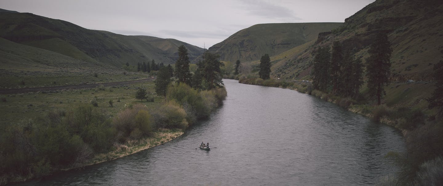 small rowboat runs downriver amid large green hills on overcast day