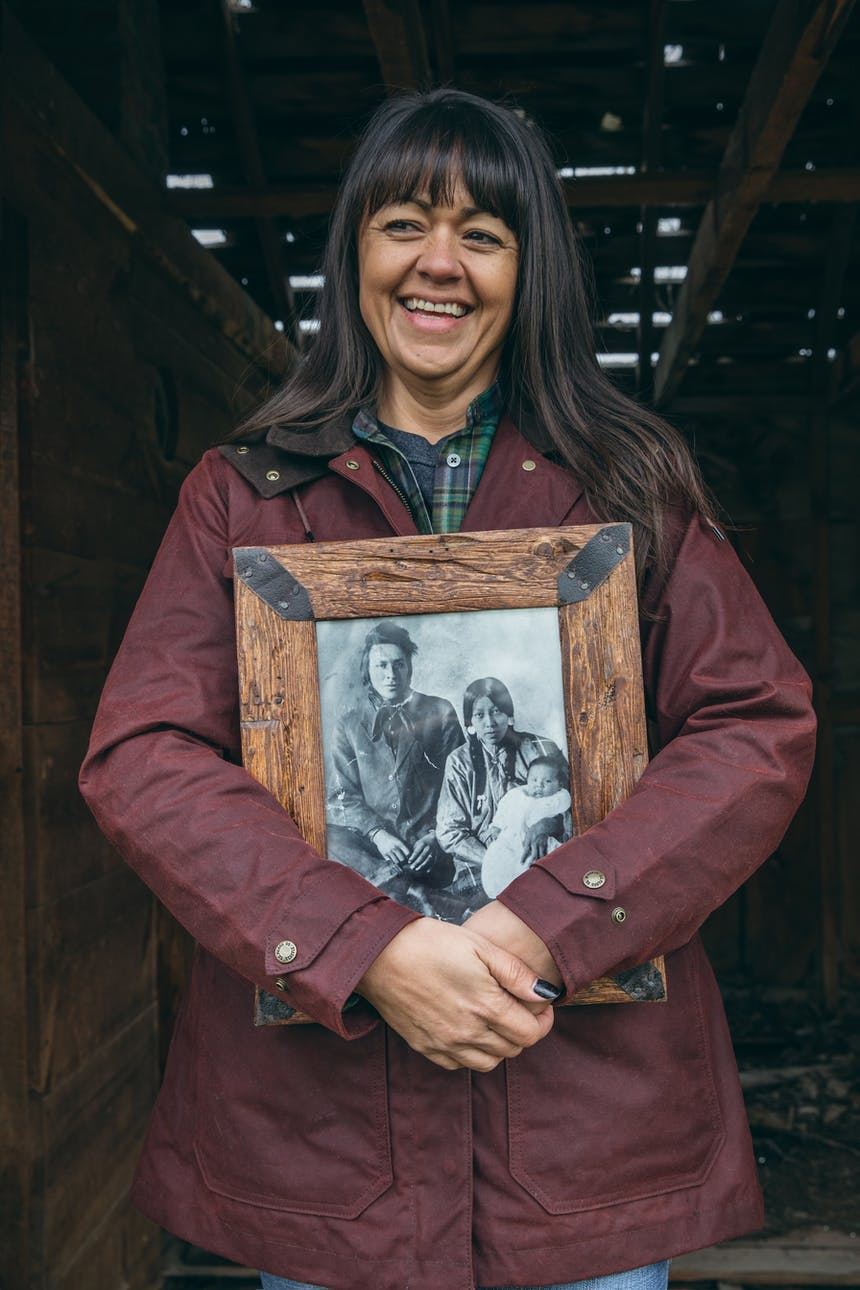 Jackie laughing, holding an old portrait of her mother and grandmother