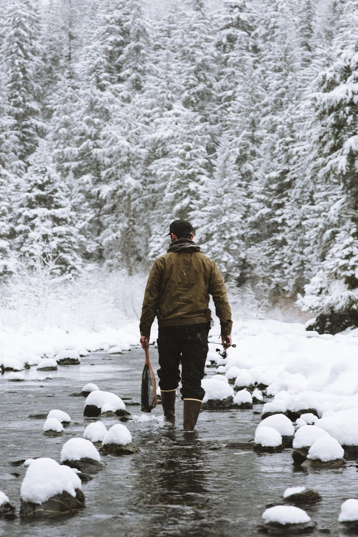 man holding fish in river with snow covered rocks and snowy pine tree forest