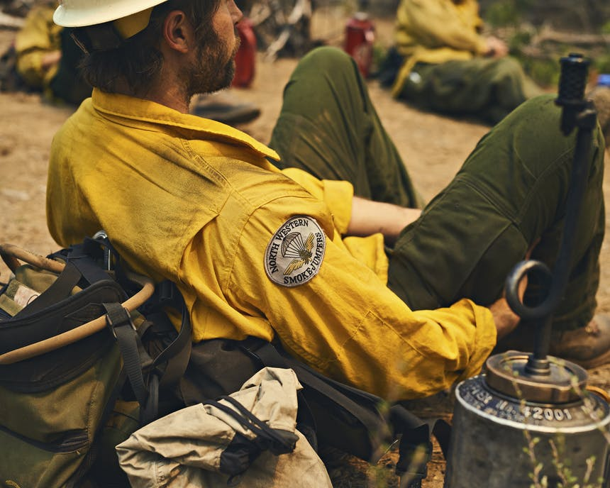 Smokejumper resting outside in yellow jacket and green pants